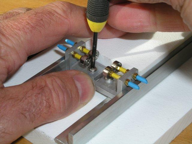 A finger will do, as you push the carriage up against the slider to true up carriage sides with base...